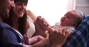 Padres en la cama que juega con la hija recién nacida del bebé almacen de video