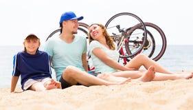 Padres felices con el adolescente en la playa arenosa Imagen de archivo