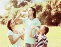 Padres felices con el agua potable del adolescente Foto de archivo libre de regalías