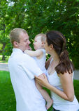 Padres felices con el bebé al aire libre imagenes de archivo