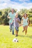 Padres felices con el hijo adolescente que juega con la bola Imágenes de archivo libres de regalías