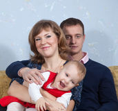 Padres felices con el niño en hogar Fotos de archivo libres de regalías
