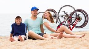 Padres felices con el niño en la playa Foto de archivo libre de regalías