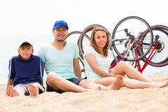 Padres felices con el niño en la playa arenosa Imagen de archivo libre de regalías