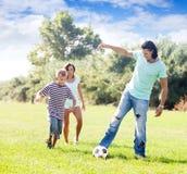 Padres felices con el niño que juega con la bola Fotografía de archivo libre de regalías