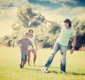 Padres felices con el niño que juega con la bola Imágenes de archivo libres de regalías