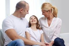 Padres felices con la pequeña hija en casa Imagen de archivo libre de regalías