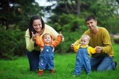 Padres felices con los gemelos imagen de archivo