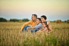 Padres felices con los niños en la puesta del sol Foto de archivo