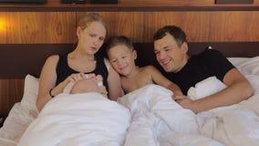 Padres felices con los niños que mienten en cama junto almacen de metraje de vídeo