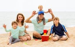 Padres felices con los niños que se sientan en la playa arenosa Foto de archivo libre de regalías