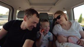 Padres felices con una más vieja hija del hijo y del bebé que tiene viaje del coche almacen de video