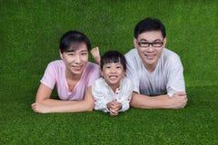 Padres felices e hija chinos asiáticos que mienten en la hierba Foto de archivo