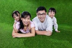 Padres felices e hijas chinos asiáticos que mienten en la hierba Fotografía de archivo libre de regalías