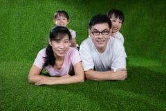 Padres felices e hijas chinos asiáticos que mienten en la hierba Imagen de archivo