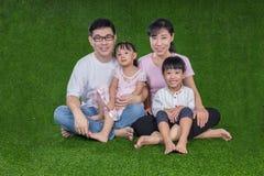 Padres felices e hijas chinos asiáticos que se sientan en la hierba Imagen de archivo
