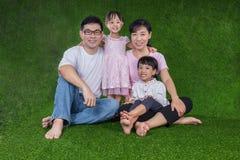 Padres felices e hijas chinos asiáticos que se sientan en la hierba Foto de archivo libre de regalías