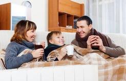 Padres felices e hijo que se calientan cerca del calentador caliente Imágenes de archivo libres de regalías
