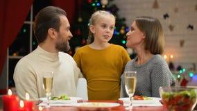 Padres felices que besan a la hija adorable el víspera de Navidad, familia que celebra día de fiesta almacen de metraje de vídeo