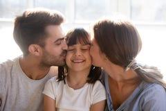 Padres felices que besan a poca hija preciosa preescolar en mejillas fotografía de archivo