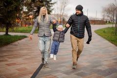 Padres felices que caminan abajo de la calle y que se divierten con un litt Fotografía de archivo libre de regalías