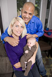 Padres felices que detienen al bebé que se sienta en el sofá en el país Foto de archivo