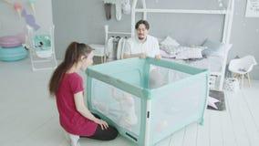 Padres felices que disfrutan al bebé que se levanta en casa almacen de metraje de vídeo