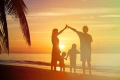 Padres felices que hacen a casa para los niños en la playa de la puesta del sol Imagen de archivo libre de regalías