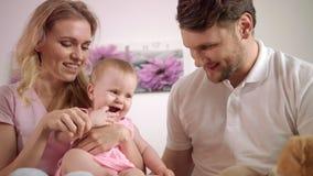 Padres felices que juegan con el bebé Retrato de la familia dulce junto almacen de metraje de vídeo