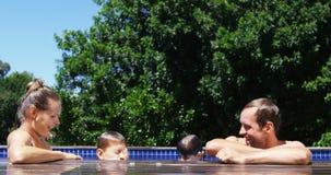 Padres felices que obran recíprocamente con los niños en piscina almacen de video