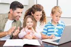 Padres felices que usan el ordenador portátil con sus niños jovenes Imágenes de archivo libres de regalías