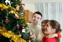Padres felices y bebé que adornan el árbol de navidad Imagenes de archivo