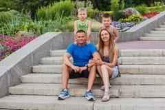 Padres felices y dos hijos en el verano en los pasos en el parque Niños que abrazan a padres foto de archivo