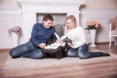 Padres felices y niño año en un traje del conejito en la sala de estar Fotos de archivo libres de regalías