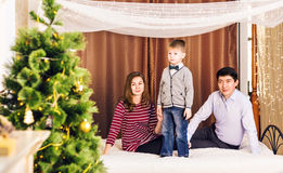 Padres felices y niño sonrientes en casa que celebran Año Nuevo Árbol de navidad Fotografía de archivo