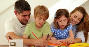 Padres felices y niños que colorean junto almacen de video