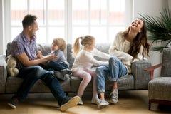 Padres felices y niños que se divierten que cosquillea sentarse en el sofá imágenes de archivo libres de regalías