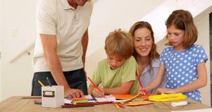 Padres felices y niños que unen en la tabla almacen de video