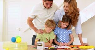 Padres felices y niños que unen en la tabla que mira la cámara metrajes