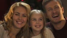 Padres felices y pequeña hija que ríen y que presentan en la cámara, humor festivo almacen de video