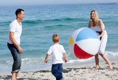 Padres felices y su hijo que juegan con una bola Imagen de archivo libre de regalías