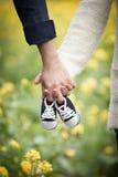 Padres futuros que sostienen manos y un par de pequeños zapatos Fotografía de archivo