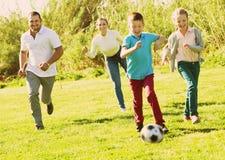 Padres jovenes con dos niños que juegan a fútbol Imágenes de archivo libres de regalías