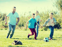 Padres jovenes con dos niños que juegan a fútbol Fotos de archivo