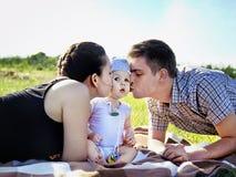 Padres jovenes con el bebé al aire libre en el parque Foto de archivo libre de regalías