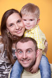 Padres jovenes con el hijo en los hombros del padre Imágenes de archivo libres de regalías