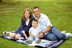 Padres jovenes con el hijo en el verano Mamá, papá y niño foto de archivo