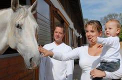 Padres jovenes con el niño y el caballo Imágenes de archivo libres de regalías