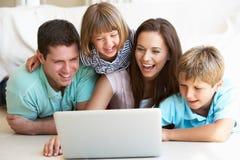 Padres jovenes, con los niños, en el ordenador portátil imagen de archivo libre de regalías
