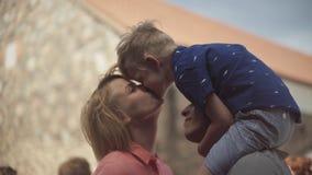 Padres jovenes con su hijo adorable que besa y que se divierte en patio metrajes